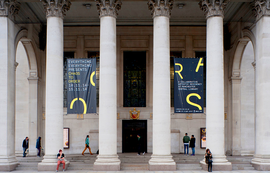 Columned entrance to classical style building, Manchester Central Library, two banners hanging between columns advertising Everything Everything - Chaos to Order.