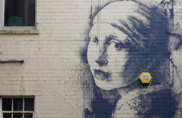 Large mural of head and shoulder of female on the side of the whitewashed brick building