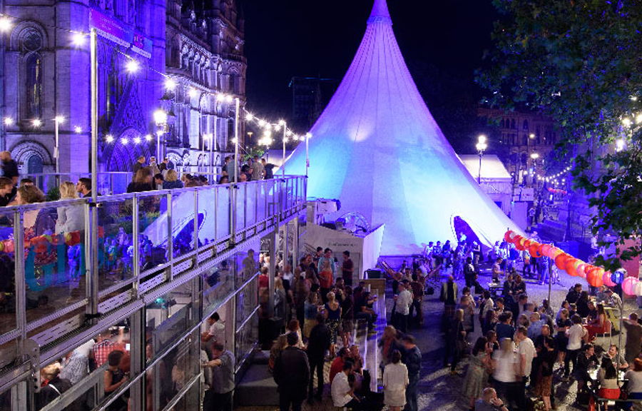 Crowded square in the evening. Large white teepee tent in the background, two storey hospitality area to the left, benched seating the right. Area decorated with red Chinese lanterns and festive lighting.