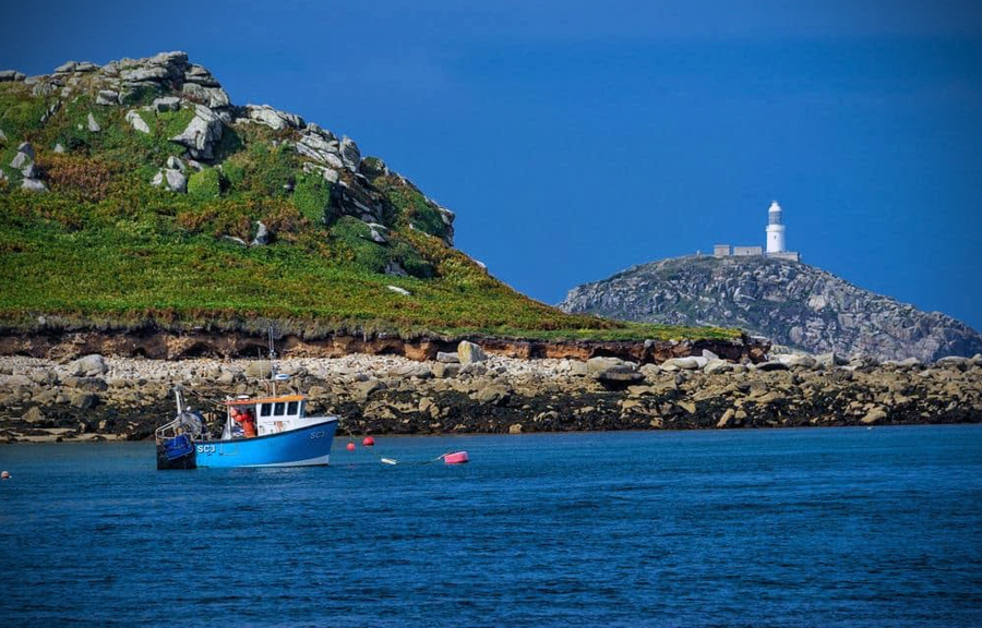 Fishing boat anchored off a rocky shore, with lighthouse in the distance.