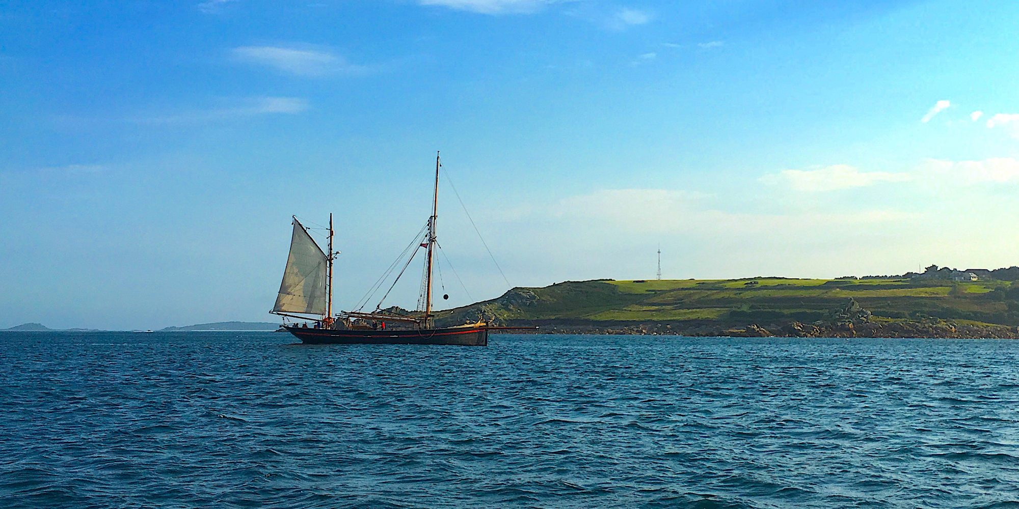 Old style, masted wooden sail boat on sea, with green landscape behind. A destination management plan for the Isles of Scilly