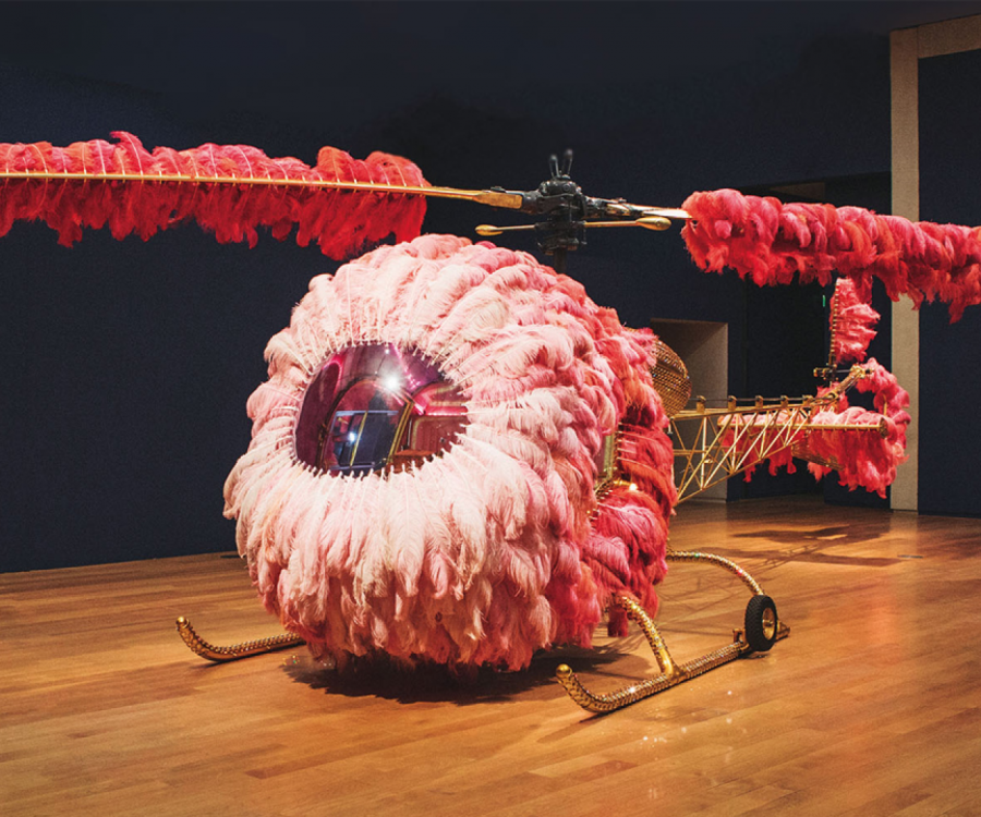 Woman looking at helicopter covered in pink feathers