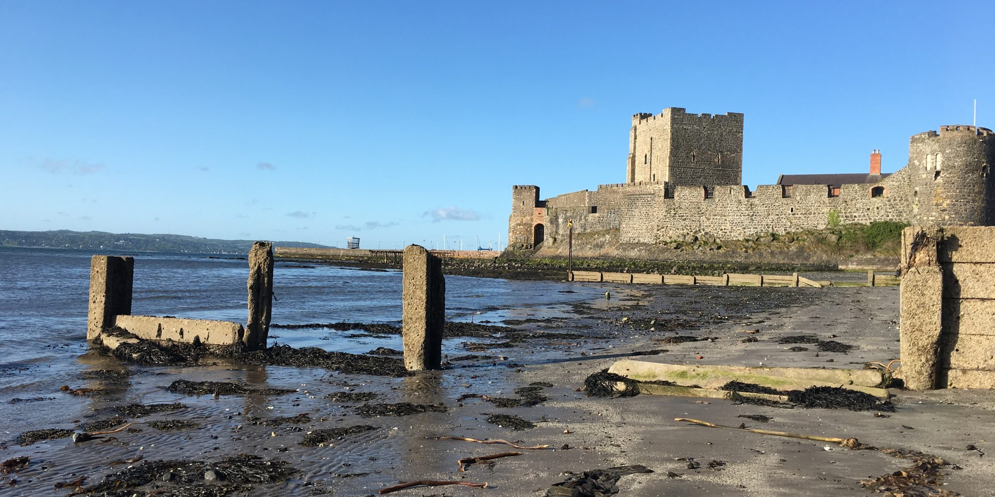 Walled castle sits on a beach, tide partly out, seaweed visible on sand