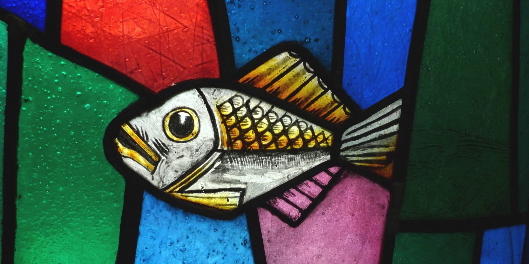 Stained glass detail of fish with decorative coloured shapes around it - Coventry UK City of Culture 2021