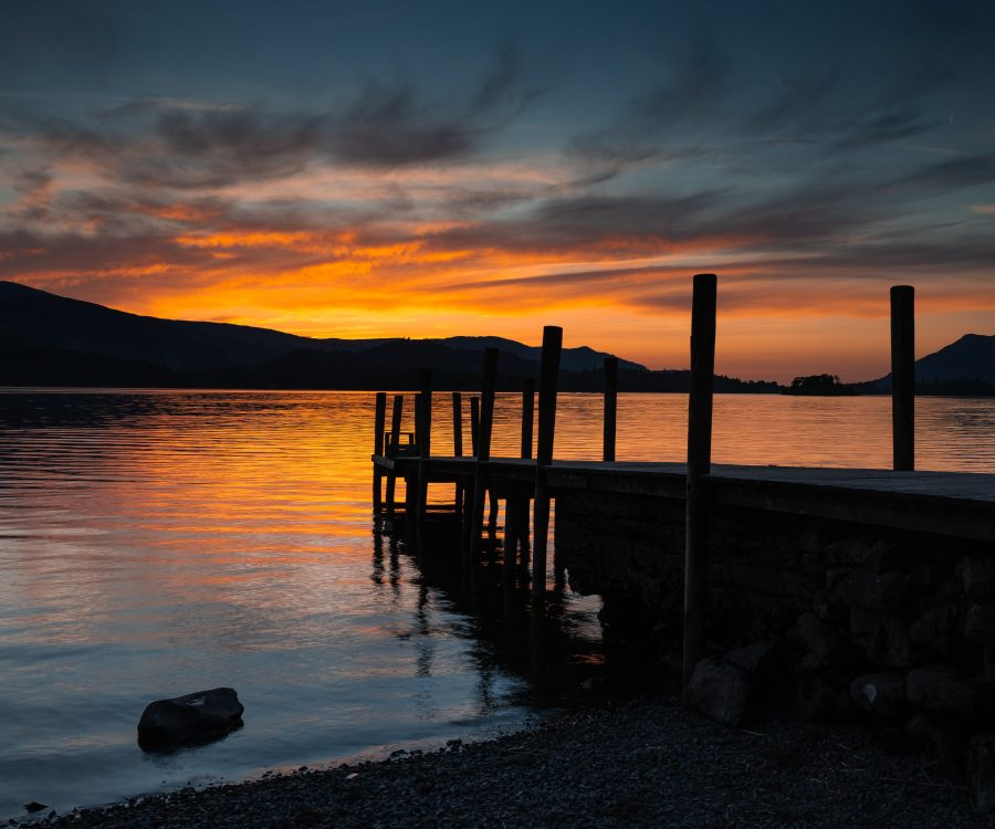 Sustainable tourism in Cumbria. Sunset over a lake, with wooden jetty in the foreground and silhouetted hills in the background