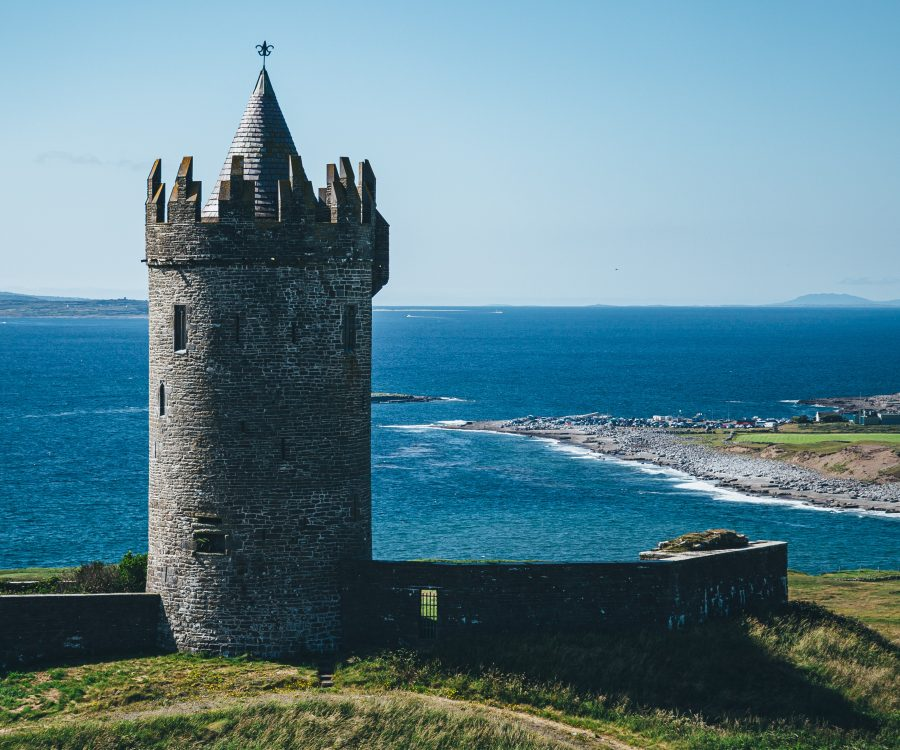Historic castle tower with coastal town and sea in the background