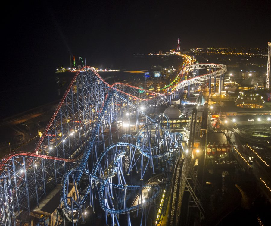 Elevated image of a rollercoaster by night, with city in the background