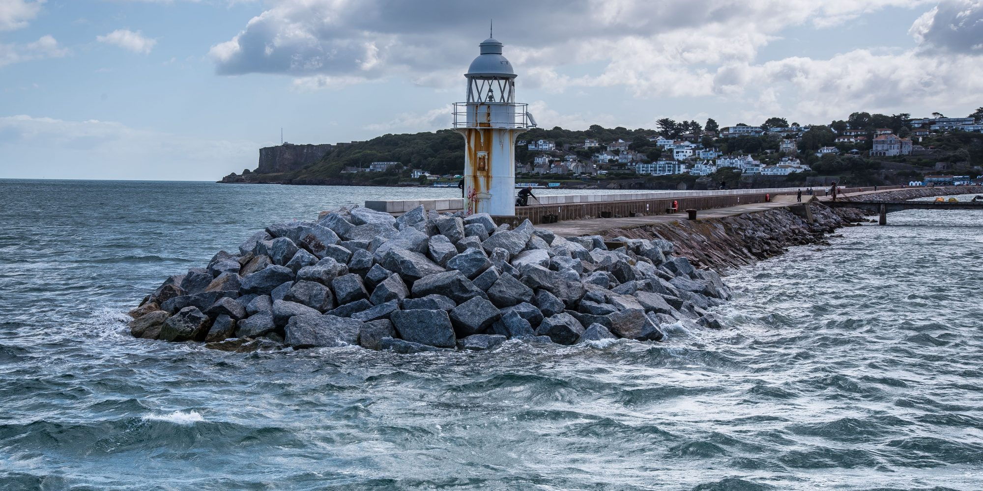 Lighthouse at end of a rocky pier, surrounded by a wild sea