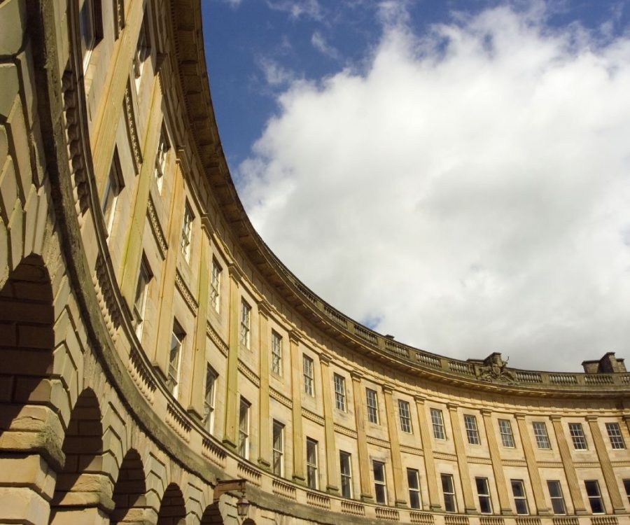 Partial detail of curved building, with cloudy sky above