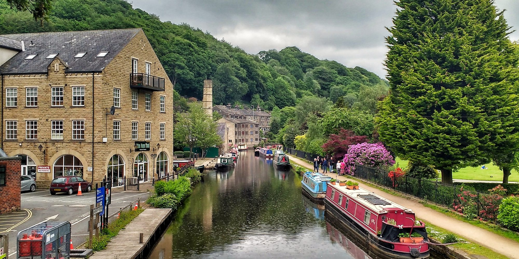 Canal with moored barges, buildings and stone chimney to the left, surrounded by trees