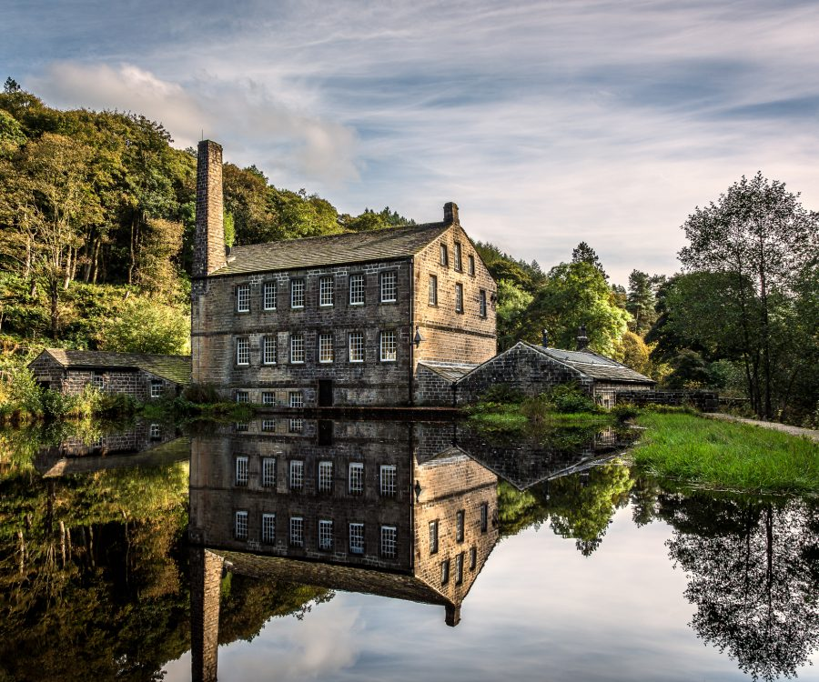 Stone mill building with tall chimney on a lake surrounded by trees