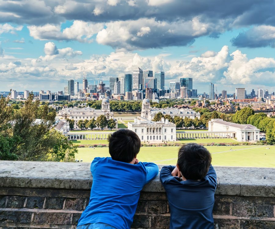 Two children looking over a park to foreground, pavilion to middle and cityscape to background