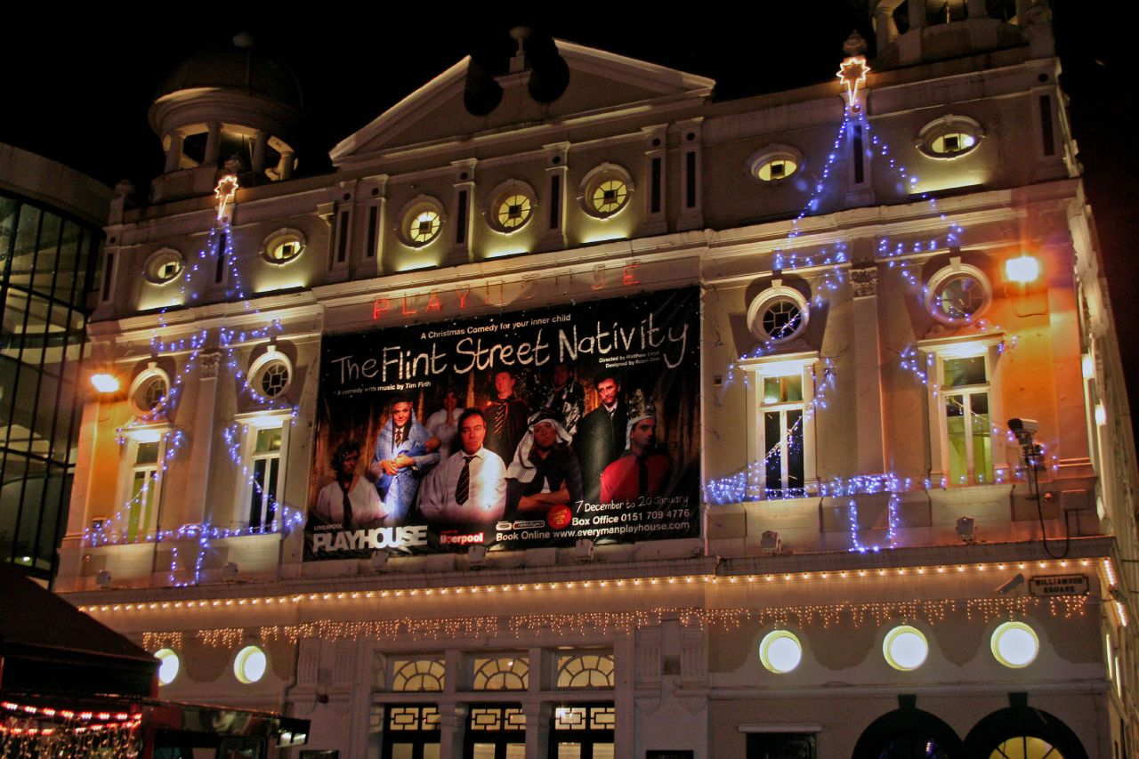 Front of theatre lit at night with Christmas neon signage, displaying signage advertising a show