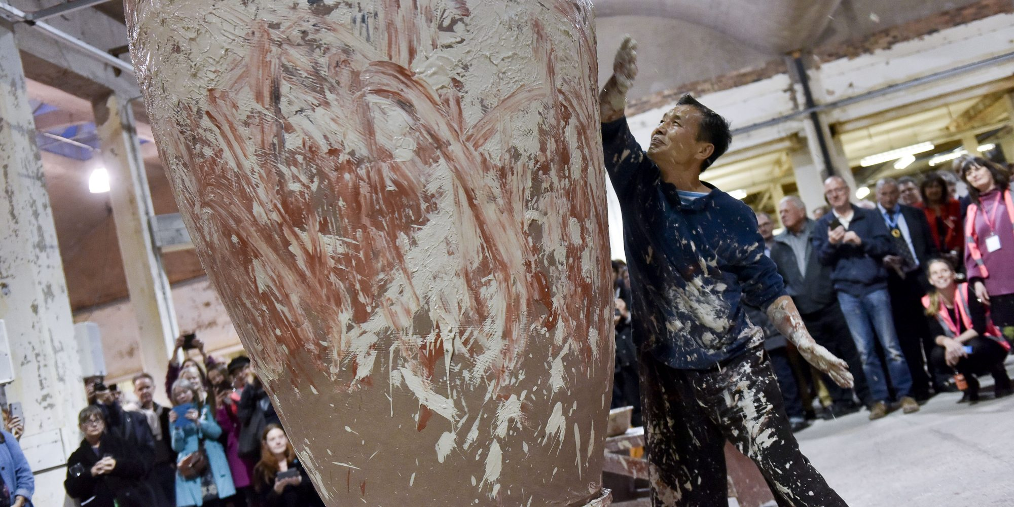 Man covered in plaster, wiping hands on large sculpture and crowd watching in background. Stoke's heritage and tourism organisations come together.