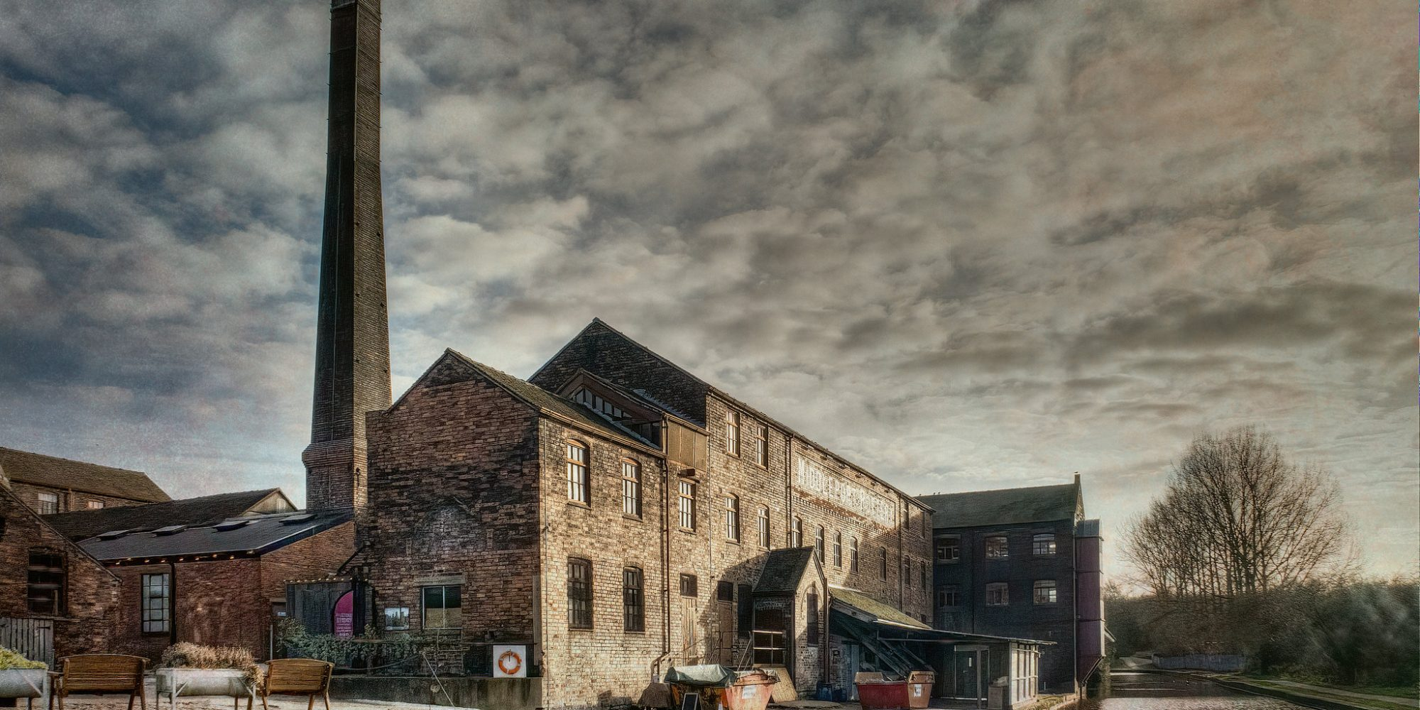 Old red bricked factory building, with tall chimney next to a river